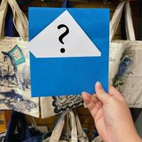 A hand holds up a blue envelope in which is visible a piece of paper with a large question mark on it.