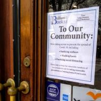 A sign regarding COVID-19 on the door at Brilliant Books
