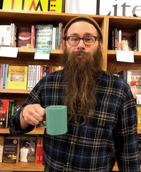 Jack smiling in front of a bookshelf at Brilliant Books