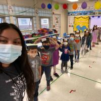 A selfie: In a bright classroom, Ms Mendoza, with medium brown skin and long  black hair, smiles behind a mask.  To her right is a line of small children wearing paper graduation caps and masks.