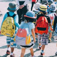 Photo of a line of children wearing colorful clothing and backpacks.