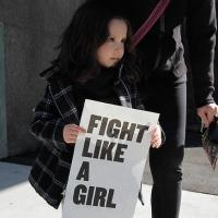 "A young girl at a protest holds a sign reading ""Fight Like a Girl"""